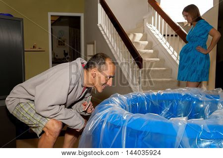 A woman in labor paces in the background preparing herself for what is to come while her husband looks eagerly at the water level in the birthing tub. He is excited she is anxious.