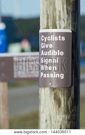 Sign warns cyclists to signal when passing on bike path along Cape Cod Canal