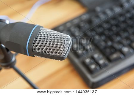Professional microphone with computer keyboard over wooden desktop surface. Podcast concept