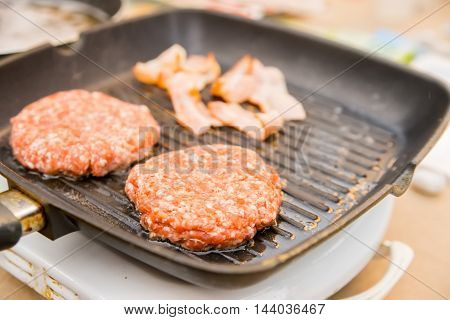 Delicious hamburger patties on a metal grill