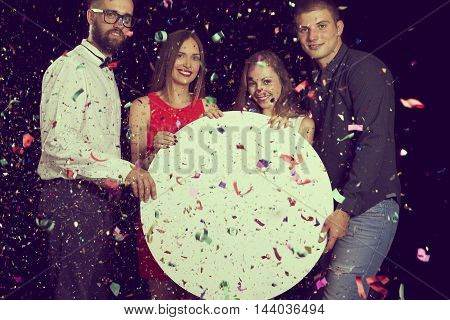 Group of friends having fun celebrating New Year's Eve and holding blank white cardboard circle