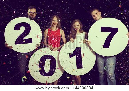 Group of beautiful young people celebrating New Year's Eve holding four cardboard circles with numbers 2017 written on them