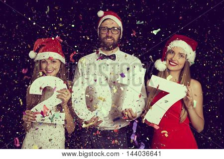 Three young friends having fun at New Year's Eve Party holding cardboard numbers 2017