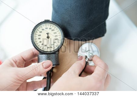 Doctor measures blood pressure of patient with stethoscope