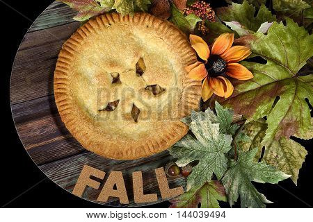 apple pie on wooden plate with fall leaves