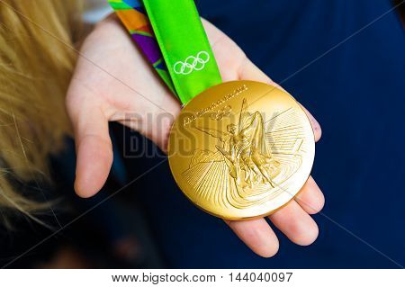MOSCOW RUSSIA - AUGUST 24 2016: Meeting with the russian women handball team.Gold medals of Olympic Games in Rio demonstration. Gold medal's obverse