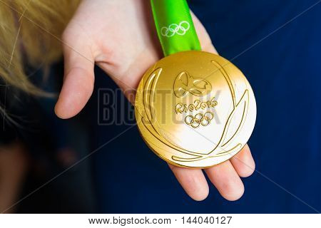 MOSCOW RUSSIA - AUGUST 24 2016: Meeting with the russian women handball team.Gold medals of Olympic Games in Rio demonstration. Gold medal's reverse.