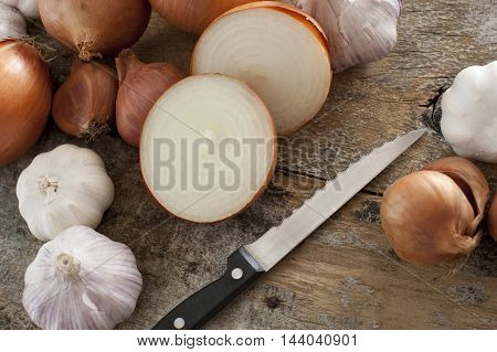High Angle Still Life of Bounty of Onions and Garlic Bulbs Being Sliced and Prepared by Sharp Knife on Rustic Wooden Table