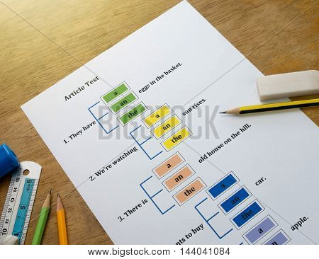 english test sheet on wooden table with stationery
