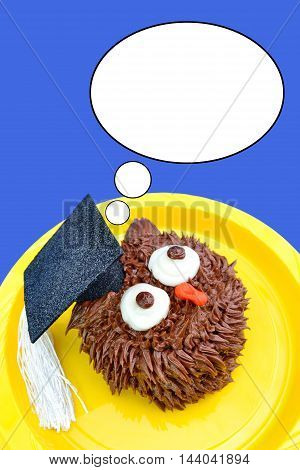A chocolate owl cupcake wears a graduation cap decoration and looks up at a thought bubble. Background is a solid royal blue color.
