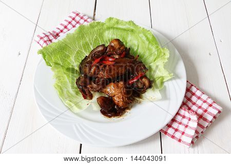 Chicken in black soy sauce on white serving plate