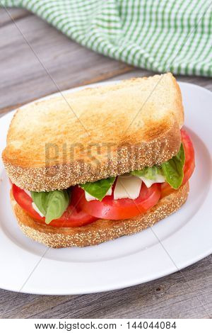 caprese tomato cheese and basil sandwich on wooden table