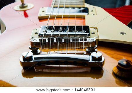 red wood guitar rock close up in dark