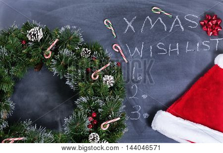 Holiday Wreath Santa cap gift bow and candy canes on erased chalkboard with Christmas wish list written on board.