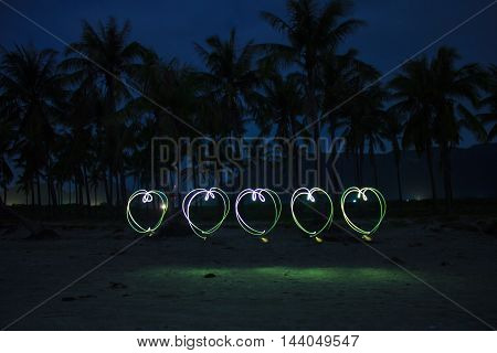 5 hearts painted on the beach with light on long time exposure of camera (bulb mode). This kind of photography is called light brush technique