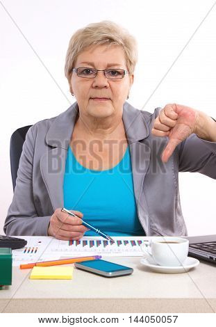 Elderly Business Woman Showing Thumbs Down And Working At Her Desk In Office, Business Concept