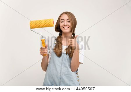 woman holding a paint roller for DIY painting.