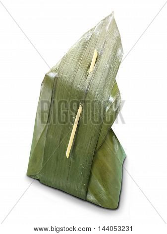 Thai dessert with coconut wrapped in banana leaves isolated on white background.