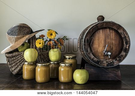 hay hat, honey jars, green happles, flowers  and a barrel