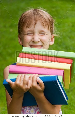little schoolgirl holding a lot of books and drops them