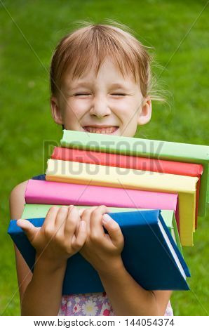 Little girl holding a lot of books and she laughs