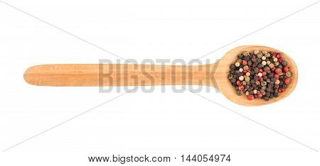 Colored pepper on a wooden spoon isolated on white