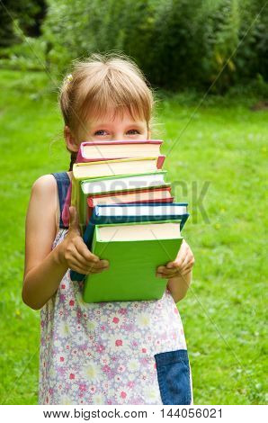 little schoolgirl holding a lot of books. preparation for school