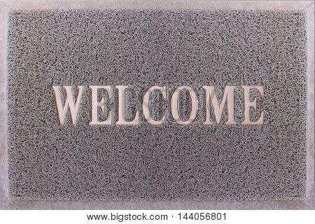 Welcome Door Mat Isolated. Friendly Grey Door Mat Closeup. Welcome Carpet. Foot Scraper Texture Background.