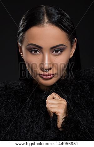 Portrait of beautiful young lady with perfect make-up in studio. Pretty model looking at camera over black background.
