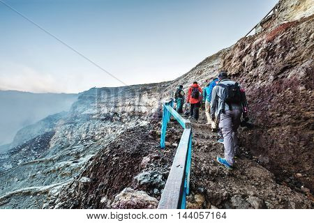 Adventurous traveler groups walking up to crater at Kawah Ijen, Indonesia