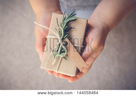 kid holding rustic gift box with brown tag holiday toning background