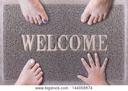 Welcome Door Mat With Three Feet and One Hand. Friendly Grey Door Mat Closeup with Bare Feet Standing. Welcome Carpet. Funny Three Feet and One Hand on Foot Scraper.