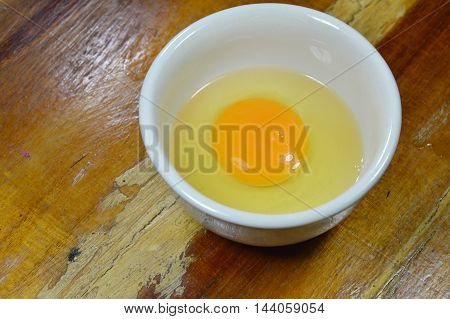 egg yolk in cup on wooden table
