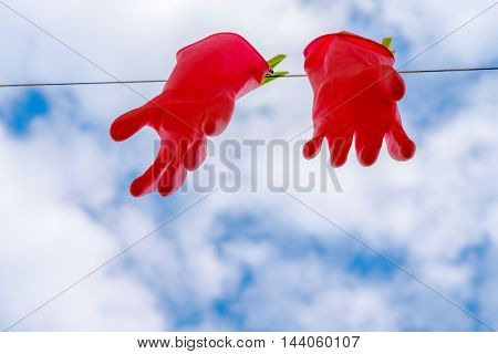 Red latex protect gloves hanging on the rope