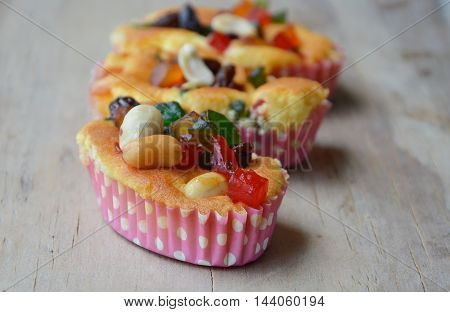 butter cupcake topping dries fruit and peanut on wooden background