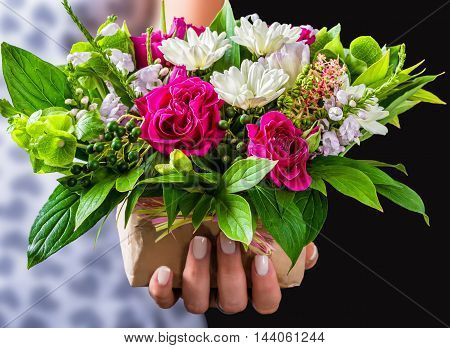 female hands holding gift and vintage wedding bouquet of rose white gerberas and greenery on black background close-up