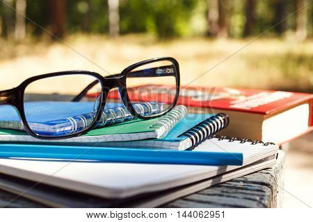 Stack of notebooks with glasses and book on bench in the park. Education background