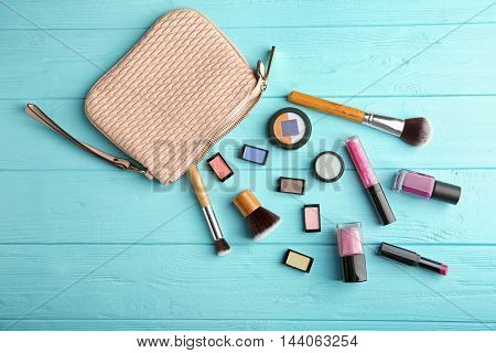 Makeup bag with cosmetic products and brushes on wooden background