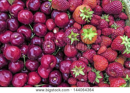ripe cherries and strawberries outdoor macro closeup