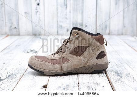 Footwear concept. A brown men's boot represented on wooden background. A boot with shoe-string sands.