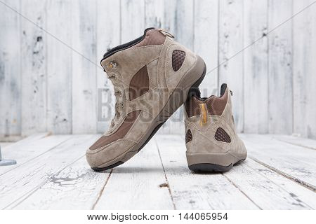 Footwear concept. A pair of leather men's boots of brown colour over white wooden background for snowy weather.