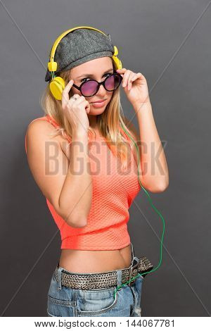 Portrait of hipster girl in earphones and sunglasses isolated on grey. Beautiful blonde posing for photographer in studio.