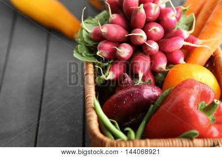 Fresh vegetables in wicker basket on table, closeup
