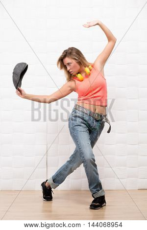 Beautiful hipster girl posing in full length while dancing in studio. Blonde demonstrating her flexible body.