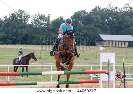 SVEBOHOV CZECH REPUBLIC - AUG 20: Front view of horsewoman during the jump-off on a brown horse at