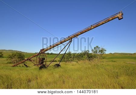 An old rust covered tube grain elevator is left in the long grass of a hilly pasture.