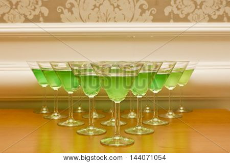 rows of green cocktails in a triangle shape on a table ready to be served