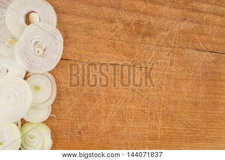 Onion rings on wooden cutting table. Top view.