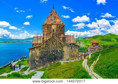 SEVAN ARMENIA - MAY 31 2016: The tourists visit Sevanavank Monastery located on Sevan Peninsula among the bright green hills on May 31 in Sevan