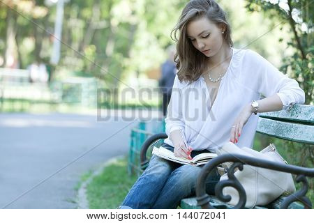Young woman taking notes while is relaxing and taking notes.